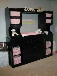 "Turn an old entertainment center into a changing table. I actually like this dark look with the pink.. but if it looks to ""monolith"" painting it the color of the walls or white could make it less massive in appearance."