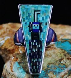 "Carl and Irene Clark Yeibechai Micro Inlay Ring #CarlandIreneClark Carl and Irene Clark are the originators of fine micro inlay jewelry. Hundreds of tiny inlaid turquoise stones create the background of this incredible ring. In the middle is a signature Yei design created out of lapis, sugilite, turquoise and onyx micro inlays. The ""Yei"" is the benevolent supernatural being who brings their healing powers to medicinal ceremonies."