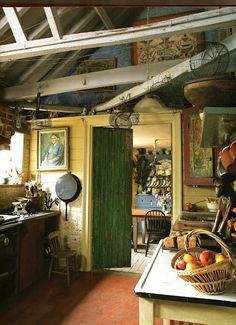 This kitchen has a lot of the things I like--beams, wire baskets hanging from the ceiling horizontal board walls, and a bit of quirkiness