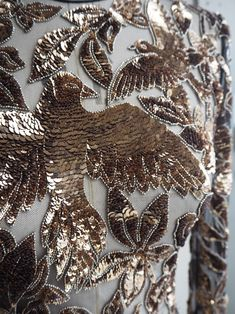 Alexander McQueen | Pre FW18 Close-up: An Autumn/Winter 2018 pre-collection dress is embroidered with doves and butterflies intertwined with wildflowers, leaves, branches and iris flowers.