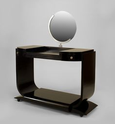 """French Art Deco ebonized dressing table with """"U"""" shaped sides over a platform base with 2 drawers and chrome trim with a round mirror"""
