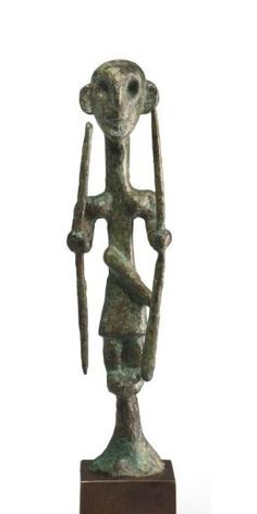 Caananite bronze warrior, Middle Bronze Age, 2nd millenium B.C. Standing with his feet together atop a high conical tenon, wearing a short kilt with his dagger at his waist, his arms held forth, each wielding a long spear, with broad shoulders and protruding pectorals, his large head with rounded ears, a prominent nose, deeply-recessed eyes and a pointed chin, 12.7 cm high. Private collection