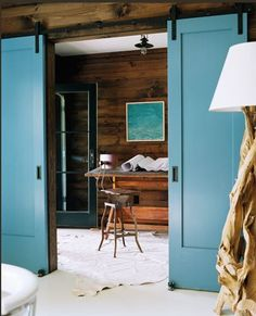 bright blue barn door. i like the contrast against the walls.