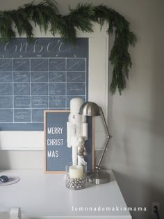 Love this neutral set-up: the white nutcracker, the fresh greenery, the letterboard, and the glass container filled with silver bells and a candle.