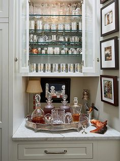 """Botherum - Off the living room is a closet complete with a bar just for bourbon. Silver sipping cups and crystal tumblers above decanters of Maker's Mark and Bulleit glisten when lit. """"It certainly makes getting dressed a whole lot more fun,"""" laughs Jon. Closet Bar, Greek Revival Home, Bar Tray, Bar Cart Styling, Butler Pantry, Bars For Home, Designer, Interior Decorating, Sweet Home"""