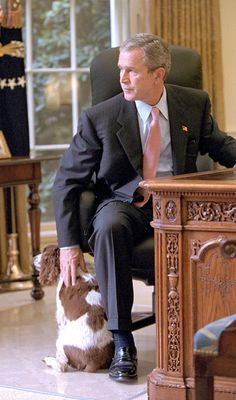 President George W. Bush petting his English Springer Spaniel Spot in the Oval Office. (Photo by Eric Draper/Mai/Mai/Time Life Pictures/Getty Images)