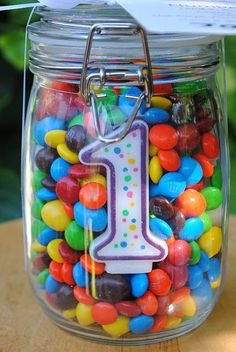 Looking for creative centerpieces for a child's birthday party? Fill a mason jar with Skittles and include a numbered candle in the front. #DIY