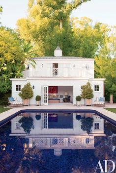 The neo-Regency poolhouse, which also functions as the guest quarters, was designed by Appleton & Assoc.   archdigest.com