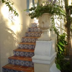 spanish tile in stairway and terracota on top for entryway, all stairs; rod iron railing
