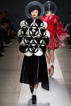 """Junya Watanabe Spring 2015 RTW – Runway – Vogueber 27, 2014 warm leatherette alongside PVC, Perspex, and the occasional jolt of tulle, and rubber swimming caps. circular shapes, volumes, and constructions— turned into """"graphic marching."""" (latest defining words of the designer.) flattened vinyl circular forms and experimental compositions, marching ever forward. But what can't be ignored in this collection. pop synthesis. graphic march of people as corporeal Tumblrs."""