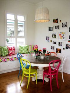 white and wood table with bright colored chairs