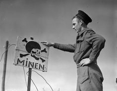 """Seaman Douglas F. Trewin of the Royal Canadian Navy Beach Commando """"W"""" points out a German sign warning of mines in the Juno sector of the Normandy beachhead - 20 July 1944    Photo by Richard Graham Arless"""