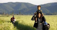 20150513 - Imigrante afegão carrega seu filho nos ombros enquanto atravessa campo na fronteira da Grécia com a Macedônia na tentativa de fugir para a aldeia fronteiriça de Idomeni em Kilkis, na Macedônia, nesta quarta-feira (13). Centenas de afegãos, sírios e imigrantes de países africanos atravessam diariamente a Grécia em sua rota para os países do norte da Europa e na sua maioria são barrados por guardas da Macedônia  PICTURE: Yannis Behrakis/Reuters