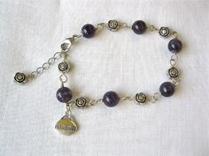 Lovely amethyst charm bracelet consisting of beads of deep mystical purple amethyst set amongst little metal flowers, and a sterling silver inspirational word charm saying 'WISDOM' ~ the quality of having experience, knowledge, and good judgement. This combination makes the perfect present for someone taking part in a competition, taking an exam or needing a calm mental attitude to achieve their goal.