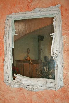 A vintage mirror with a plain wooden frame is transformed using driftwood.
