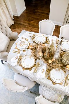 The most wonderful time of the year! Family holiday dinner! Elegant Christmas Table Scape with white lace tablecloth, gold flatware, gold garland, mercury glass votives, gold trees, gold chargers and white and gold monogrammed plates
