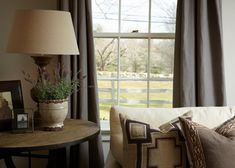French Country style is rustic and comfortable. Gray curtains soften the windows, while a mix of neutral fabrics in linens and burlaps is paired with distressed woods.