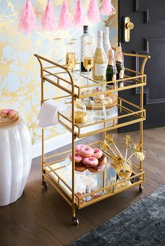 With two clear glass storage shelves and a mirrored bottom shelf that accommodates tall bottles, Pier 1's Gold Square Bar Cart can become party central for your New Year's Eve gathering. Its wrought iron frame and golden finish give the room a luxe look, especially if you drape it in Pier 1 Glimmer Strings®.