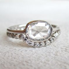 Rose cut oval diamond 18K white gold ring by Sarah Perlis. Stunning. Love the low profile rose cut diamond and that it calls for a curved band to match.