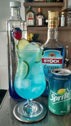 * LAGOA AZUL * - 25 ml. Vodka - 50 ml. Licor Curaçau Blue - 01 Limão Tahiti - SPRITE® - 01 Cereja (para decoração) - Coloque a vodka, o licor curaçau blue e o suco de meio limão em uma taça Hurricane com gelo e mexa bem. - Corte a outra metade do limão em rodelas, separe uma para decoração, corte-as pela metade e coloque na taça. - Complete com a sprite. - Decore com uma rodela de limão e uma cereja.