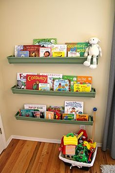 Rain gutter bookshelves painted green. Wonder if chalkboard paint would work on these?! Then I could label the books by genre, author, etc.