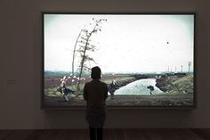 A visitor viewing Jeff Wall's 'A sudden gust of wind (after Hokusai)' 1993