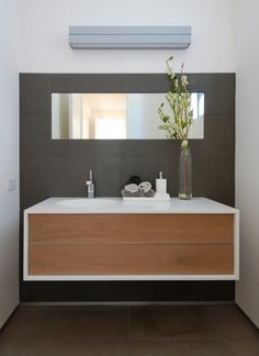 Once you decide to go for the floating vanity element, have some fun with the finishes you pick. The white and wood vanity against a dark gray wall is a decidedly contemporary selection of finishes.