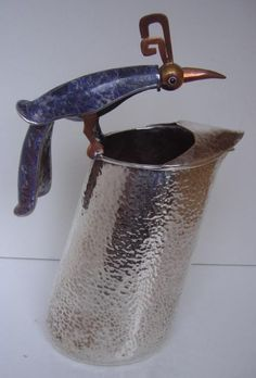"""Los Castillos, Taxco hammered plateado, (silver over copper), pitcher with a lapis lazuli stone and mixed metal handle in the form of a perching bird. The underside is marked """"Los Castillos, Taxco, Mexico. Measures 11.75"""" tall."""