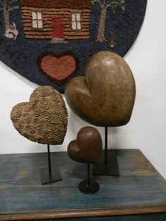 Carved wood hearts mounted and displayed in front of a heart shaped hooked rug (on a primitive blue chest)