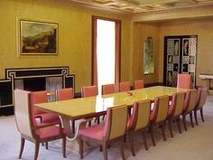 This interior at Eltham Palace features cubist pattern repeating at the ceiling to the door and fireplace. The black lacquer doors feature the white cubist/greek pattern and feature stylised animals. Rectangular shaped table and window dominate the room.