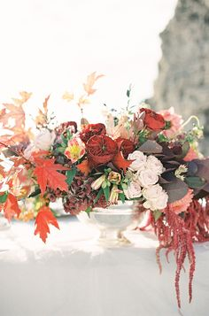 Warm Coastal Wedding Inspiration. Red wedding centerpiece.