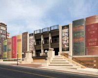 Very neat! The Community Bookshelf is a striking feature of Kansas City's downtown. It runs along the south wall of the Central Library's parking garage on 10th Street between Wyandotte Street and Baltimore Avenue. The book spines, which measure approximately 25 feet by 9 feet, are made of signboard mylar. The shelf showcases 22 titles reflecting a wide variety of reading interests as suggested by Kansas City readers and then selected by The Kansas City Public Library Board of Trustees.