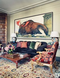 Presiding over the library is an artwork by Walton Ford; the antique armchair is clad in a Sabina Fay Braxton velvet, the cocktail table is from Charles Jacobsen, and the antique rug is from India.