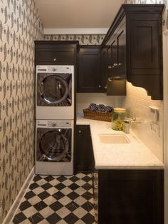 stacked washer & dryer + counter top + black cabinets + marbled checkerboard floor