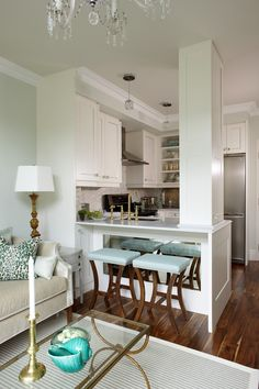 A beautiful small kitchen that opens up to family room. The support column is also a cabinet. Design by Sarah Richardson. Cool use of the mirror by bar stools
