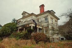 """""""Hatchet"""" Harry Flavel's House  This home is falling into ruin because the Flavel descendants refuse  to sell it, despite many interested buyers. Mr. Flavel stabbed someone  here in the 80's and became a fugitive from the law, leaving it  abandoned forever."""