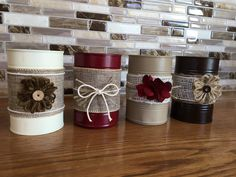 Set of four recycled and up cycled tin cans. These cans are painted and decorated with ribbon, flowers and bows for a rustic/country feel. They can be used as vases, candle holders, kitchen utensil holders, or organizers for odds and ends. They were opened with a Pampered Chef can opener, so they do not have a sharp edge. Please also keep in mind that they are tin cans, so each can may be slightly different and may have minor dents. Thanks for looking