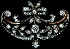 An Elegant Belle Epoque Diamond Brooch Pin Made in Moscow between 1908 and 1917  This finely handcrafted vintage brooch is designed in garland style of the 1910s.    The brooch / pin is set with old mine, Old European and rose cut diamonds with approximate total weight of 2 carats. The center diamond is approximately 0.5 ct.  The diamonds are set in silver over 14K rose gold. Width - 40 mm (1 5/8 in.).  Height - 28 mm (1 1/8 in.).