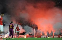 Arsenal forward Alexis Sanchez walks away from the stands as flairs are thrown on to the p...