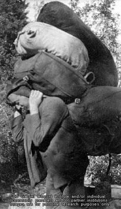 Member [Métis ? JE] of the New Northwest Exploration expedition carrying a large amount of supplies on his back at a portage at Waterhen Lake, SK, 1909. THE VIRTUAL MUSEUM OF MÉTIS HISTORY AND CULTURE.
