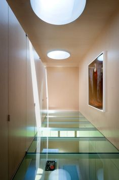 Salt Point House by Thomas Phifer and Partners.  Hallway with millwork storage and glass floor looking down onto the kitchen.