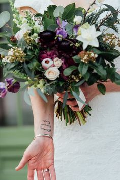 Beautiful photo of bride showing off her tattoo (strong, brave, true) and winter flower bouquet made up of white, green, purple, and pink flowers. Willowdale Estate, a weddings and events venue north of Boston, Massachusetts. WillowdaleEstate.com | Erica Ferrone Photography