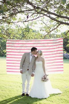 pink and white striped photo booth backdrop  Photography by craigsandersphotography.co.uk