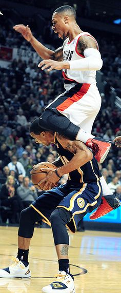 Damian Lillard jumping George Hill . That's a cute photo shot right there .