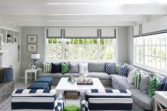 Gray and blue living room with green accents features a large gray sectional topped with green and blue pillows located under windows dressed in blue grosgrain roman shades and framed by gray walls complementing white wood ceiling beams.