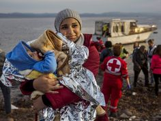 A Syrian woman holds her baby after their arrival on a small boat from the Turkish coast on the northeastern Greek island of Lesbos.