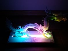 3D puzzle dragon made in 2mm white acrylic and illuminated with 30 neopixels led controled with arduino. The idea for the model I got from the project http://www.thingiverse.com/thing:2700 I rescaled everything to fit in acrylic thickness 2mm. In some parts I changed the dimensions of slot thickness  to better merged. The original model has the right front leg in the air but acrylic is very brittle and I changed the design so that the right leg is identical to the left leg, it is less…