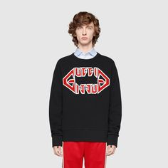 In a silhouette that has become synonymous with the House, the logo is displayed in a bold graphic font that is reminiscent of heavy metal bands from the '80s. For the Cruise 2019 fashion show, Gucci staged a rave party among the ancient graves of Alyscamps' Roman necropolis, in Arles. Walking a runway divided by flames, in the spectral setting the models played rock stars sporting looks that brought back the mainstays of '80s glam metal.  Black stone washed heavy felted cotton jersey Metal Gucc Gucci Sweatshirt, Graphic Sweatshirt, Glam Metal, Heavy Metal Bands, Rock Stars, Rave, Roman, Cruise, Fashion Show
