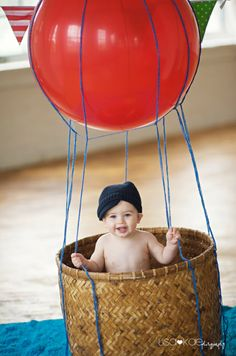 baby in a hot air balloon.DIY Hot air balloon, with native wicker basket and some yarn and balloon.