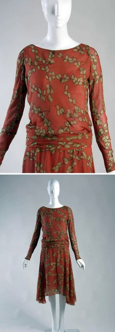 Day dress, Chanel, 1925. Orange-red printed silk crepe with pattern of green leaves edged in gold-colored embroidery. Wide, scooped neck. Blousing effect at dropped waist. Long, narrow sleeves with snaps at cuffs. Hem is higher in front than on sides. Chicago History Museum